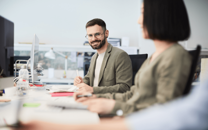 Tweemedewerker,één man en één vrouw met elkaar in gesprek achter een bureau
