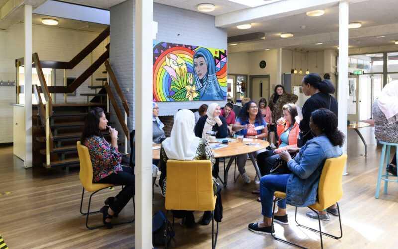 Groep volwassenen in zaal met meerdere tafel gezellig met elkaar in gesprek