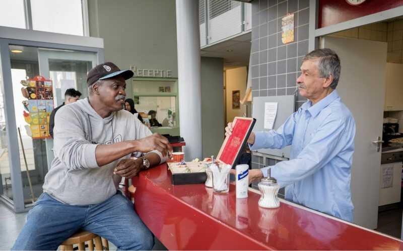 Twee heren één voor en één achter de balie met elkaar in gesprek met een bakkie koffie erbij
